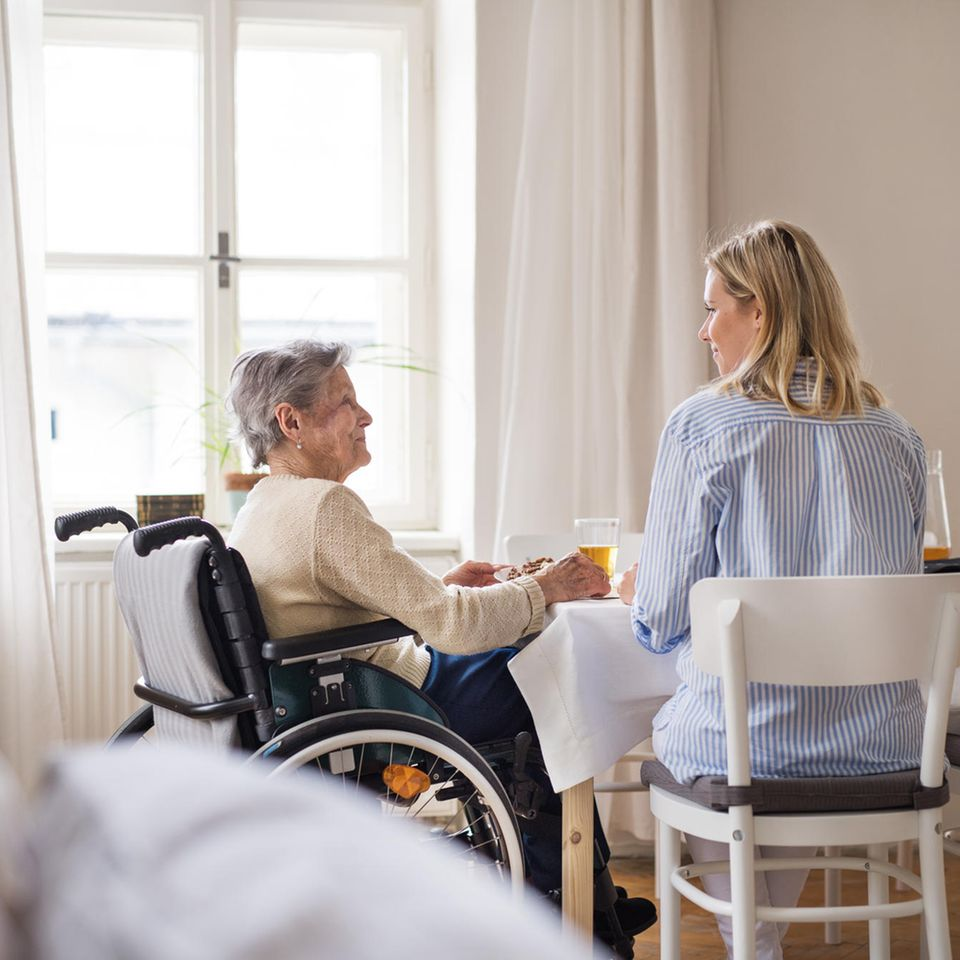 Pflege der Eltern: Ältere Frau im Rollstuhl sitzt mit jüngerer Frau am Tisch