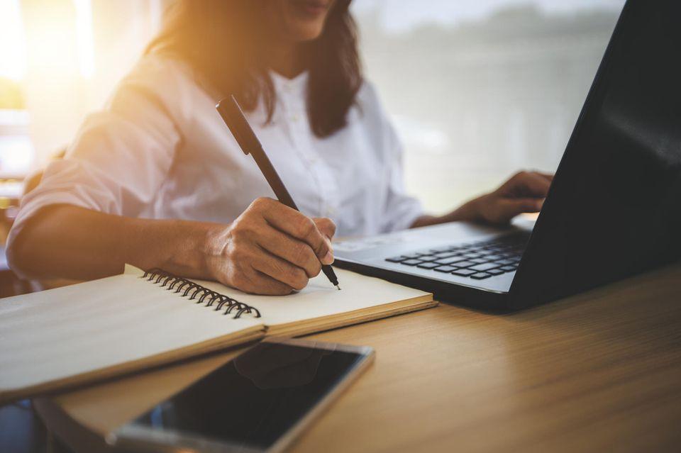 Weiterbildung: Frau sitzt mit Notizblock am Laptop
