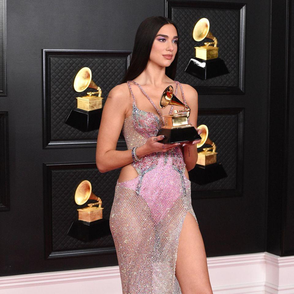 Ist das ein Kleid oder ein Schmuckstück? In diesem Kleid vonVersace posiert Dua Lipa mit ihrem Grammy. Passend zum Kleid gibt's natürlich den passenden Schmuck vonBVLGARI. Mehr Glamour geht nicht!
