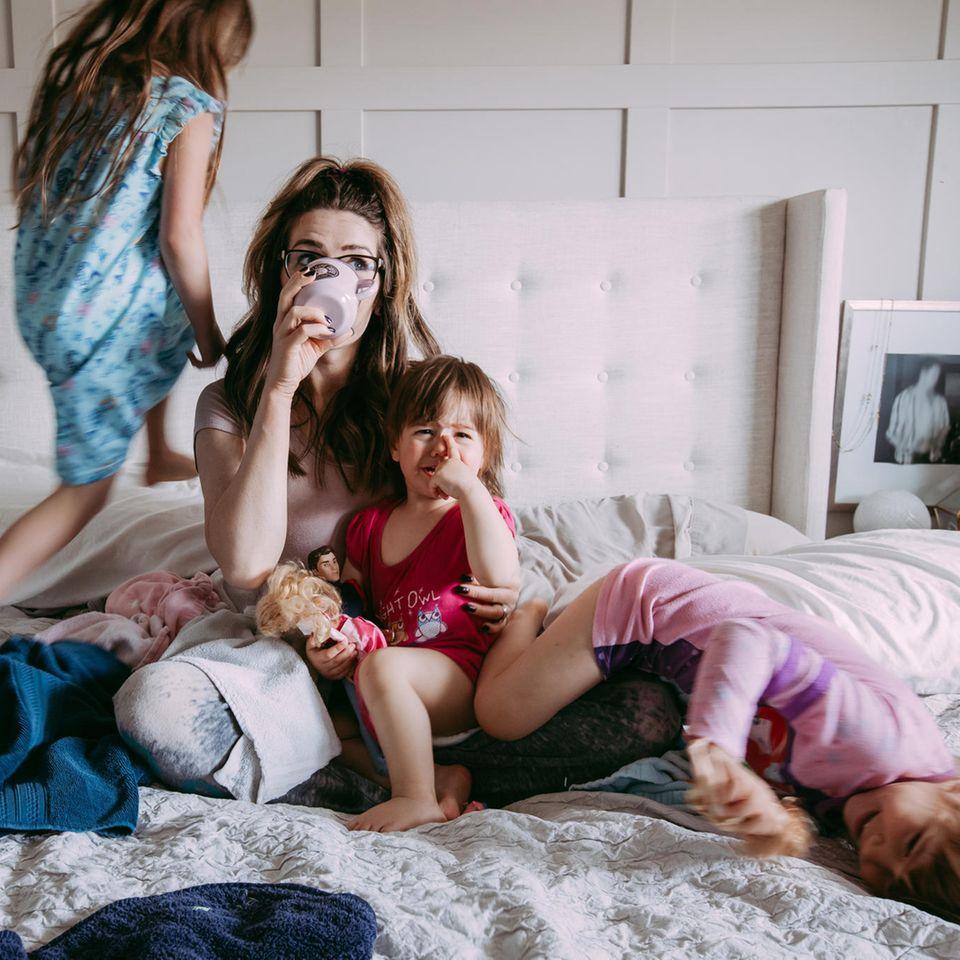 Mutter mit Kinder auf Bett