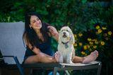 Bester Freund der Frau: Frau sitzt mit Hund auf Sonnenliege