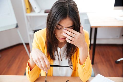 Quarter Life Crisis: Gestresste Frau sitzt am Schreibtisch.