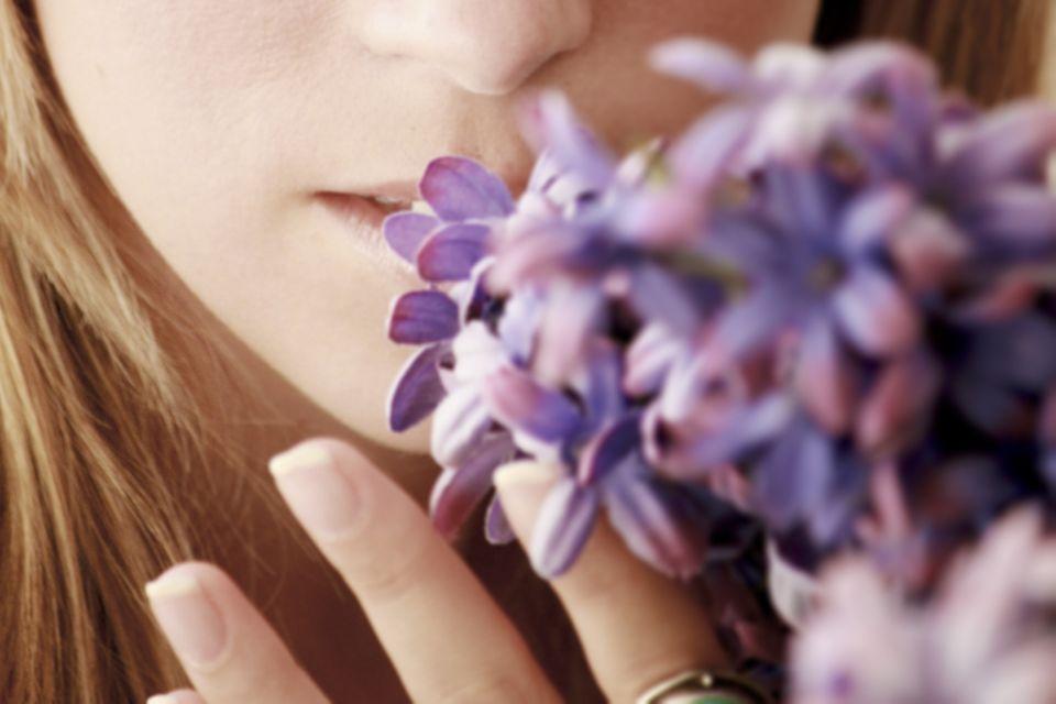 Geruchssinn: Frau riecht an Blumen