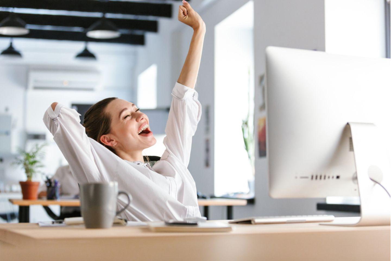 Motivationssprüche: Frau sitzt am Schreibtisch und jubelt.