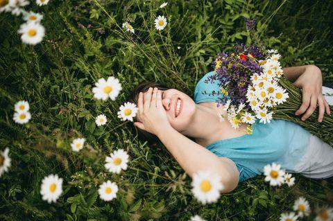 Horoskop: Eine lachende Frau liegt auf einer Blumenwiese