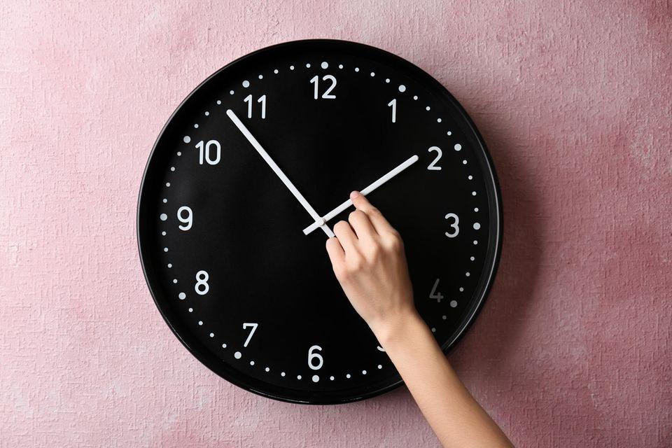 Zeitumstellung: Frauenhand an Uhr