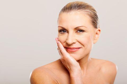 Schöne Frau im mittleren Alter berührt ihr Gesicht