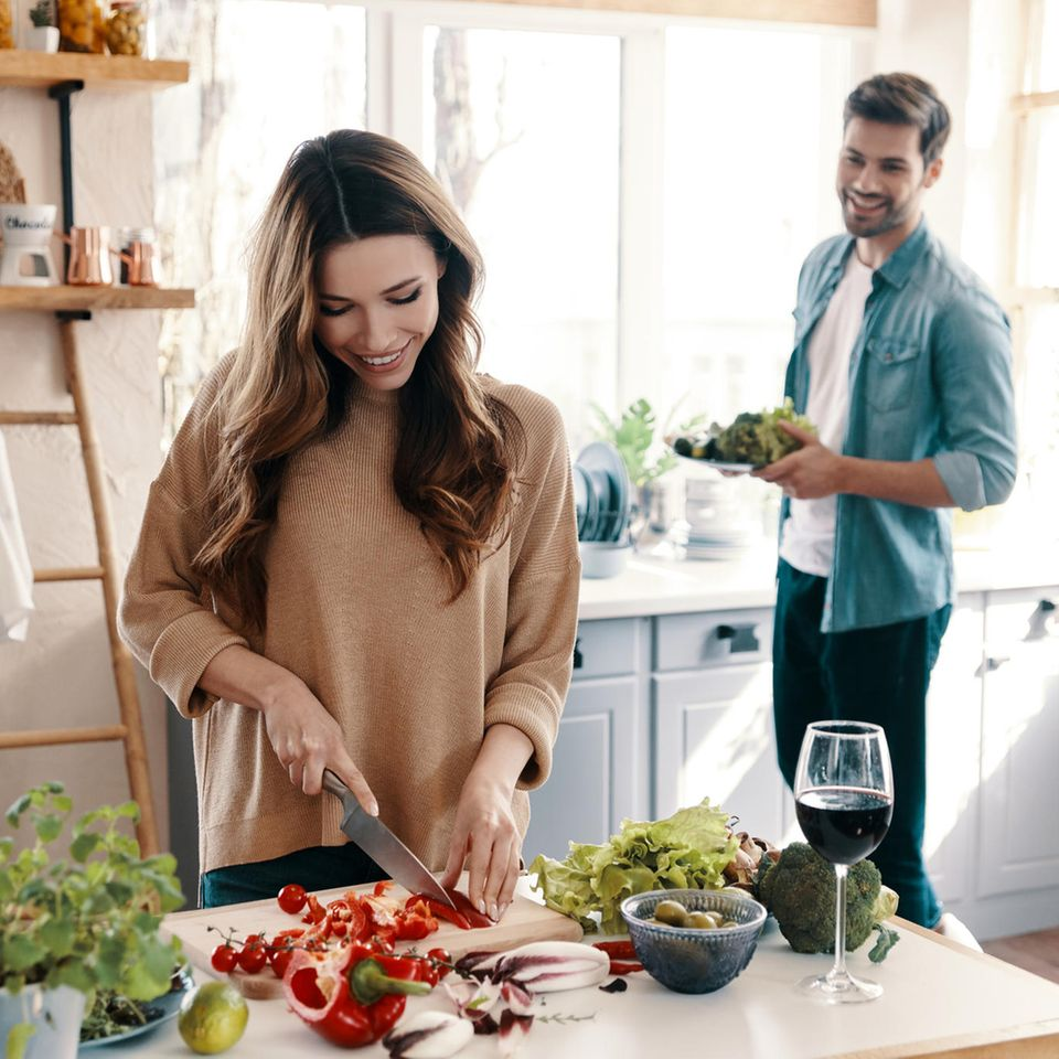 Küchengadgets: Paar am Kochen, Frau schneidet Gemüse, glückliches Paar in der Küche