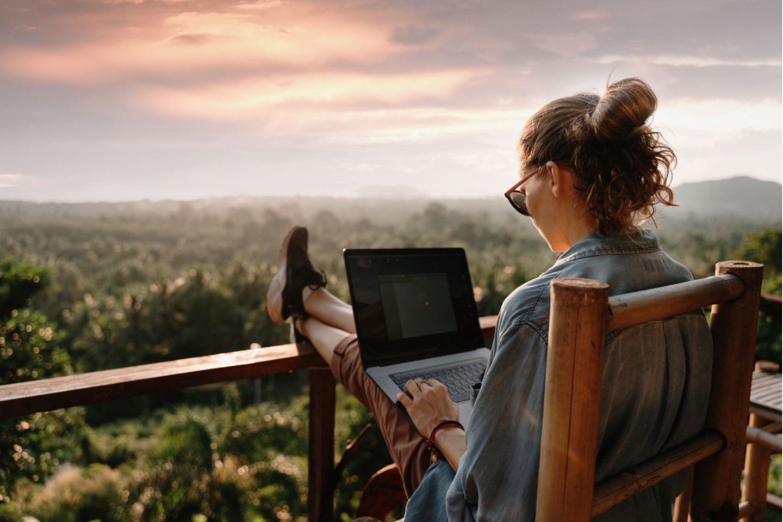 Remote Work: Frau sitzt auf dem Balkon und arbeitet.