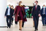"""Königin Máxima scheint eine neue Lieblingsfarbe in ihrem Kleiderschrank zu haben! Immer wieder sieht man die Königin der Niederlande in verschiedenen Rottönen. Besonders Outfits in Bordeauxrot haben es ihr aktuell angetan. Bei der Eröffnung der 10. nationalen """"Week van het Geld"""" setzt sie auf ein Etuikleid mit passendem Mantel und kombiniert dazu knallig gelben Schmuck, der für einen tollen Farbkontrast sorgt."""