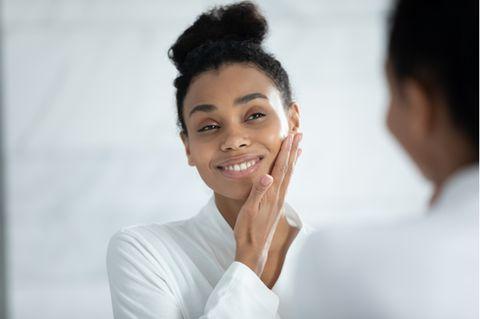Schöne Frau benutzt Pflegeprodukt im Gesicht