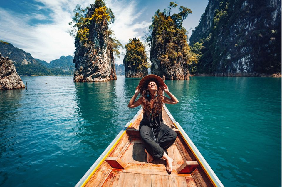 Huna: Glückliche Frau im Boot vor tropischer Landschaft.