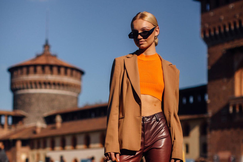 Model mit orangem Oberteil und brauner Hose
