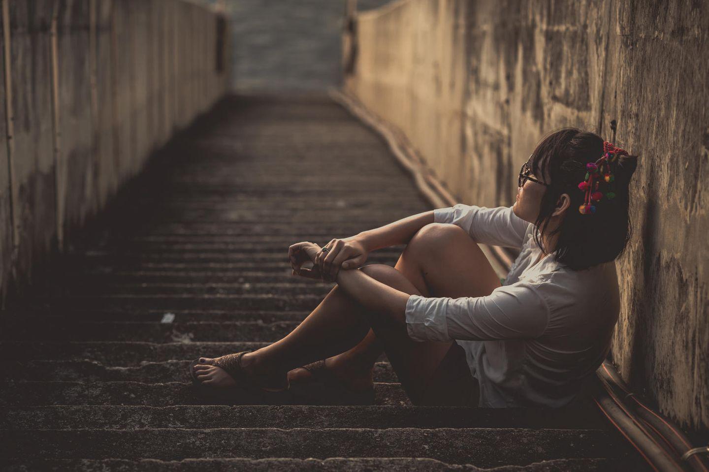 Psychologie: Eine traurige Frau auf einer Treppe