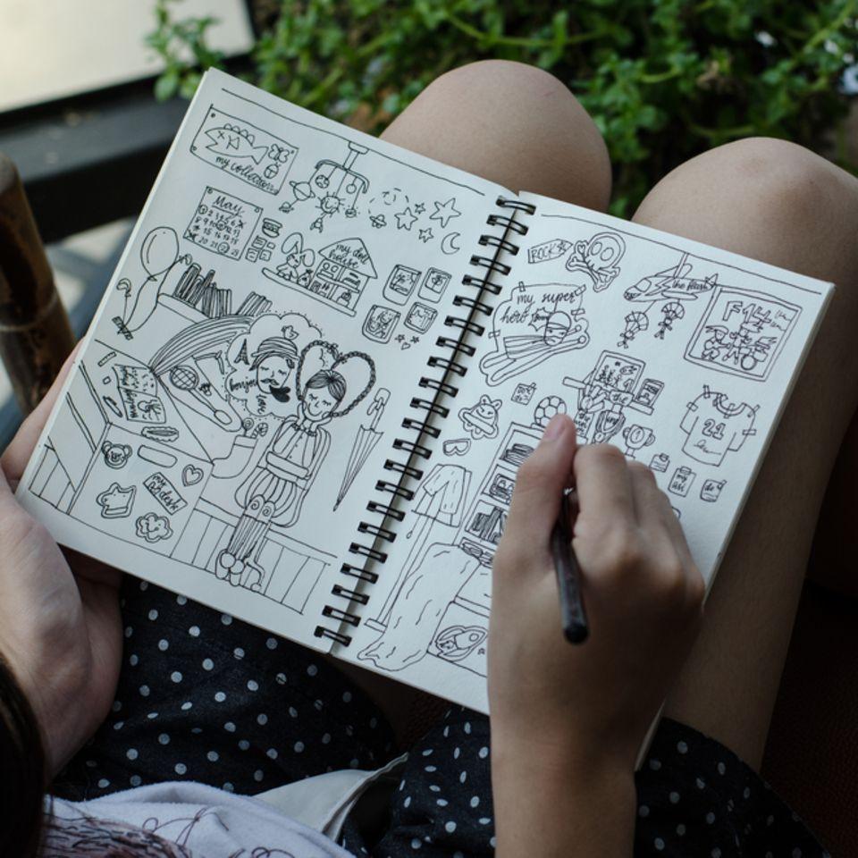 Doodles zeichnen: Junge Frau sitzt mit Zeichenblock auf dem Schoß
