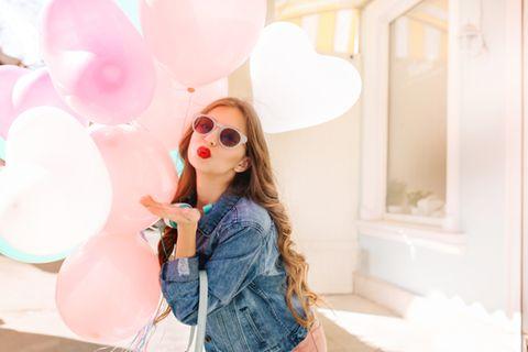 Emophilia: Frau hält Herzluftballons und macht einen Kussmund