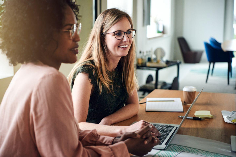 Mimik: Zwei Frauen beim Arbeiten am Laptop.
