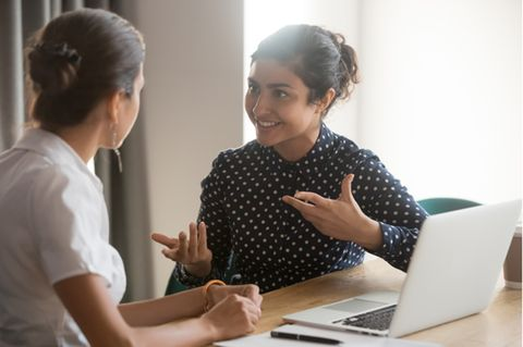 Gestik: Frau gestikuliert im Gespräch mit einer Kollegin.