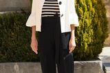 Es istklassischer Schwarz-Weiß-Look, den uns Königin Letizia hier präsentiert. Doch Letizia weiß genau, auf was sieachten muss, damit das Outfit nicht eingestaubt oder langweilig wirkt. Das spanische Oberhauptsetzt auf raffinierte Schnitte. So bekommt die Hose mit ihrem Schleifendetail am Bund und der Blazer mit seinen Volants und großen Knöpfen einen modernen Twist. Wir merken uns also: Klassiker gerne, allerdings in einem modernen Schnitt oder mit einem spannenden Detail.