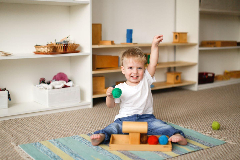 Montessori Kinderzimmer: Kind spielt mit Holzspielsachen