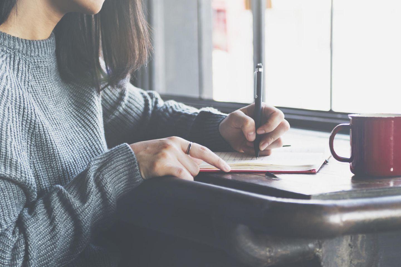 Corona-Tagebuch einer Mutter: Frau schreibt in ein Tagebuch