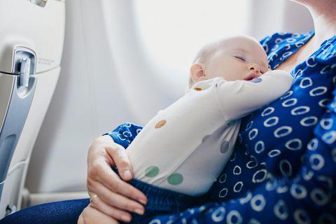 Fliegen mit Baby: Mutter sitzt mit Baby im Flugzeug