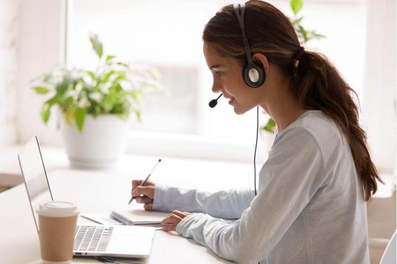 Berufe mit Zukunft: Frau mit Headset sitzt vor dem Laptop