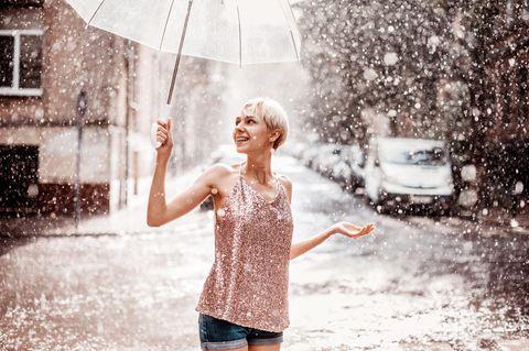 Horoskop: Eine leicht bekleidete Frau mit Schirm im Schnee