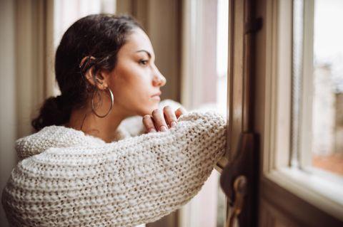 Frau nachdenklich am Fenster