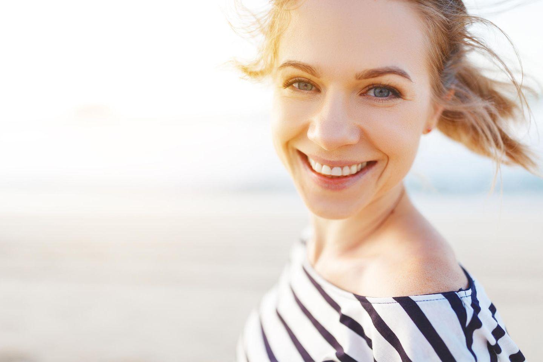 Gender Immun Gap: Frau lachend am Strand