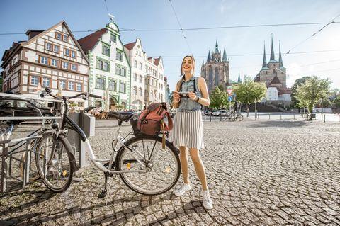 Urlaubsziele in der Nähe: Junge Frau steht mit Fahrrad auf sonnigem Marktplatz