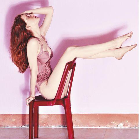 Pflanzenhaarfarbe: Frau auf Stuhl mit roten Haaren