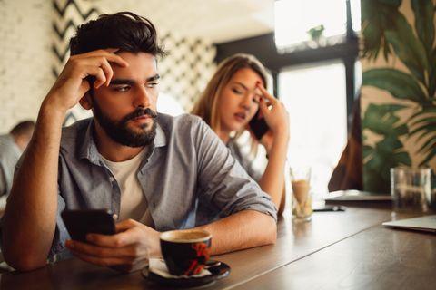 TikTok: Frau sitzt genervt am Tisch, Freund ist am Handy