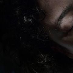 """Nora Klein: Das ist während derselben Fotosession mit Anke (roter Pullover) entstanden. Sie lag in ihrem Zimmer auf dem Boden, das Licht der Sonne fiel auf ihr Gesicht. Dieses Spiel mit Licht und Schatten hat eine dramaturgische Wirkung. In der Ausstellung wird dieses Bild überdimensional groß gezeigt. Das verdeutlicht die Wucht und Schwere der Erkrankung."""""""