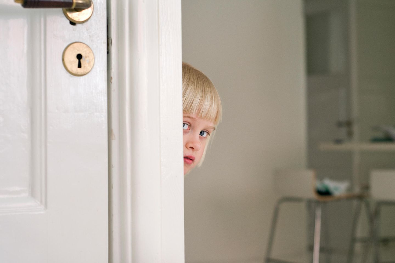Kind schaut hinter Tür hervor