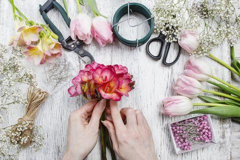 Frühlingsdeko basteln: Frau bastelt mit Blumen