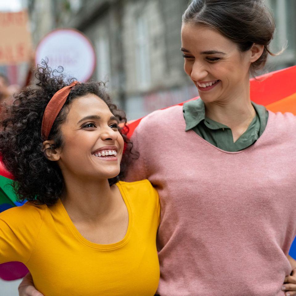 LGBTQ+-Fakten: 2 Frahen mit der Pride Flagge