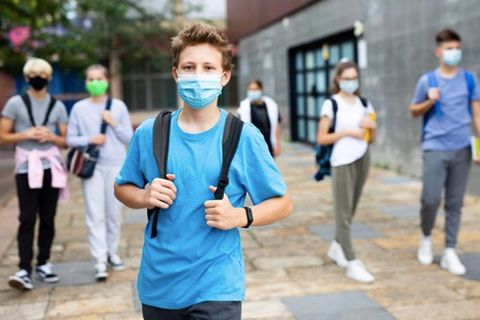 Corona-Impfstoff für Kinder: Junge auf Schulhof mit Maske