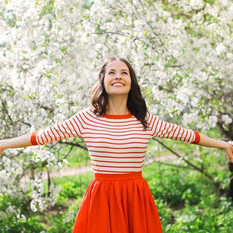 Selbstliebe-Sprüche: Frau mit ausgebreiteten Armen vor einem blühenden Apfelbaum.