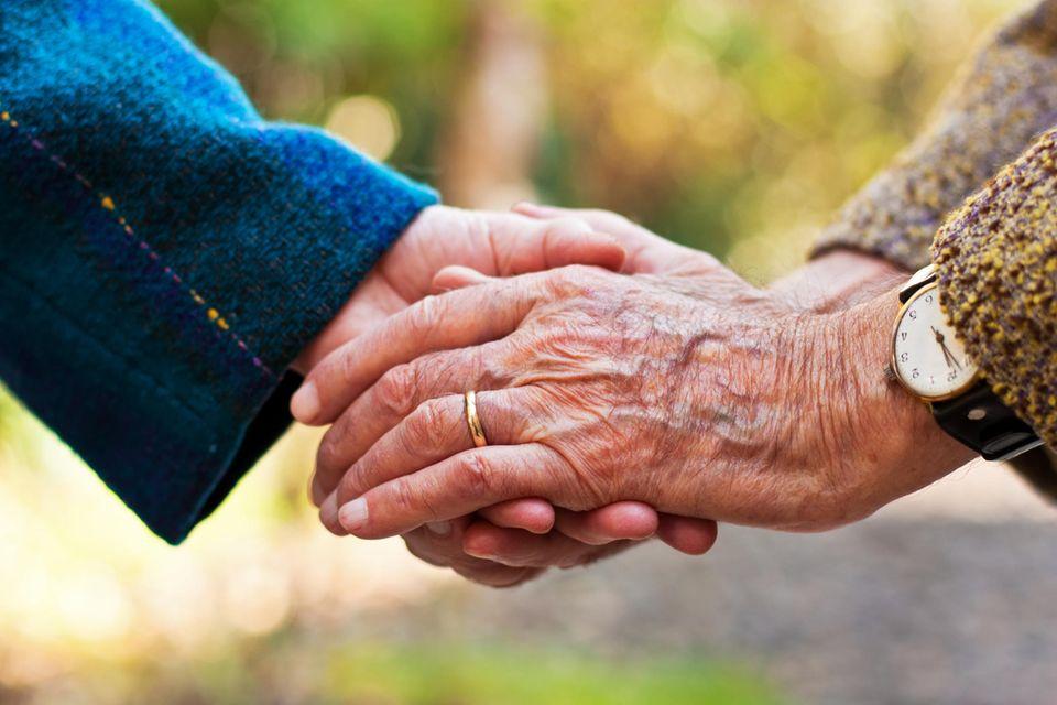 Wegen Corona getrennt: Hände mit Ehering, die sich fassen