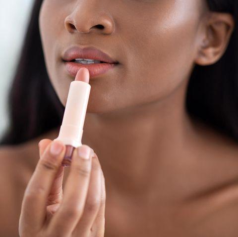 Lippenstift matt: 3 Produkte für jeden Hautton, eine junge Frau schminkt sich die Lippen