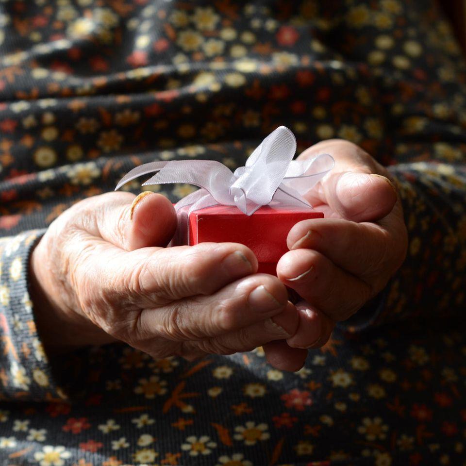 Corona aktuell: Ältere Frau mit Geschenk