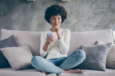 Priming: Frau sitzt im Schneidersitz auf der Couch und grübelt.