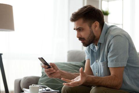 Fake-SMS: Mann am Handy, geschockt