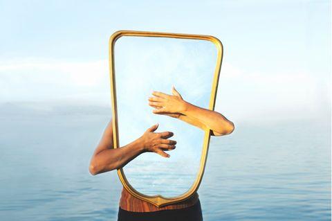Selbstwahrnehmung: Frau hält einen Spiegel vor ihren Körper