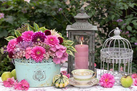 Garten dekorieren: Blumen und Windlicht auf einem Gartentisch