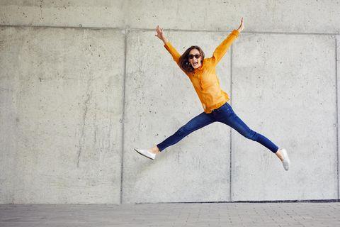 Horoskop: Eine fröhliche Frau springt durchs Bild
