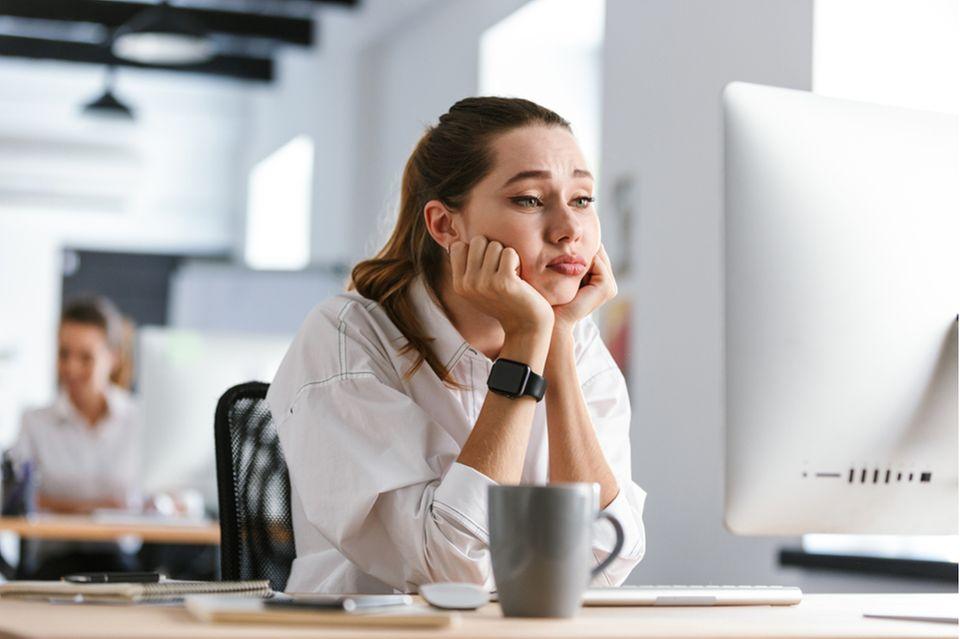 Extrinsische Motivation: Frau sitzt am Schreibtisch.