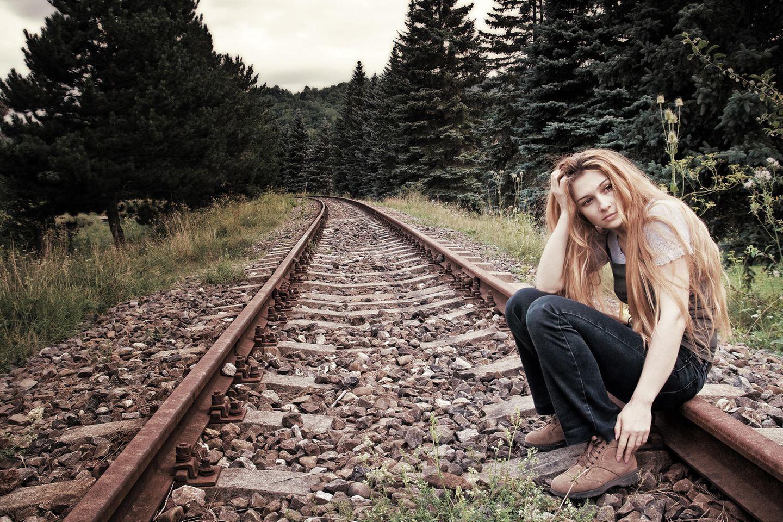 Beziehung:Eine nachdenkliche Frau auf einer Bahnschiene
