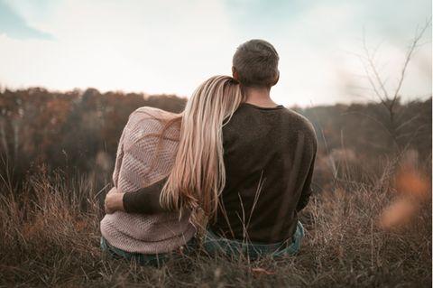 Emotionale Abhängigkeit: Frau und Mann sitzen im Gras nebeneinander